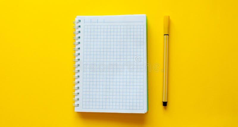 Тетрадь школы с карандашем на желтой предпосылке Пустая страница тетради для входного сигнала текст в середине Взгляд сверху, дел стоковое изображение