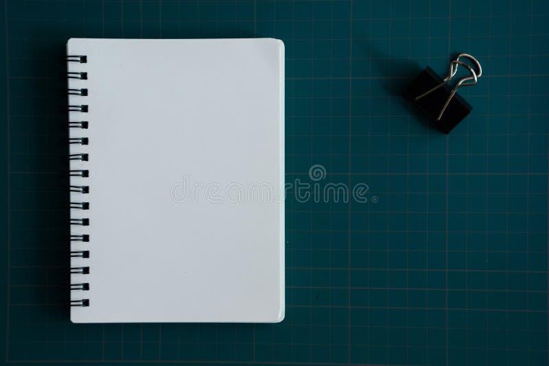 Тетрадь и бумажный зажим на разделочной доске стоковые фотографии rf