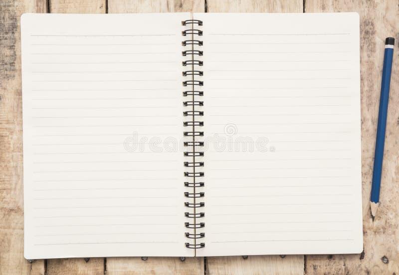 Тетрадь и карандаш на деревянном столе стоковые фото