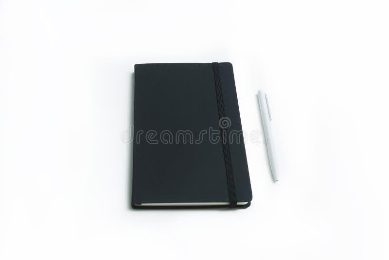 Тетрадь и ручка белизны стоковая фотография rf