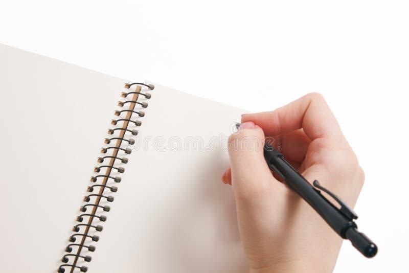 Тетрадь и ручка в руке белизна изолированная предпосылкой стоковые изображения rf