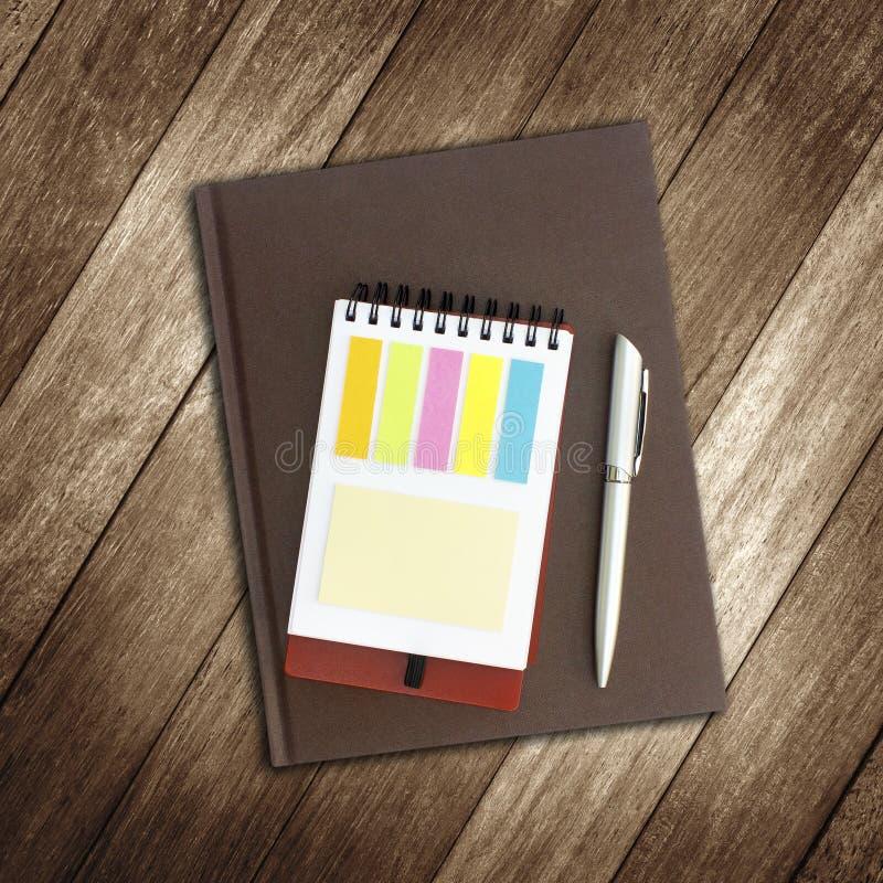 Тетрадь и ручка на деревянной предпосылке стоковые фото