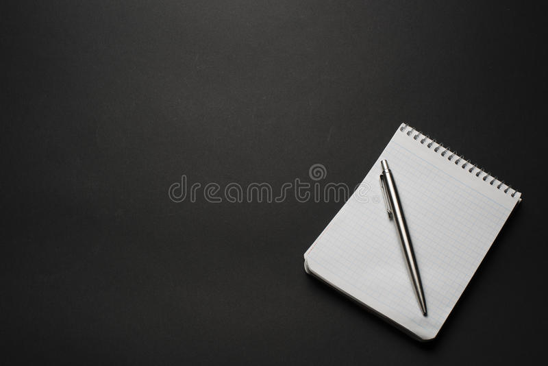 тетрадь и ручка на черной таблице стоковые фотографии rf