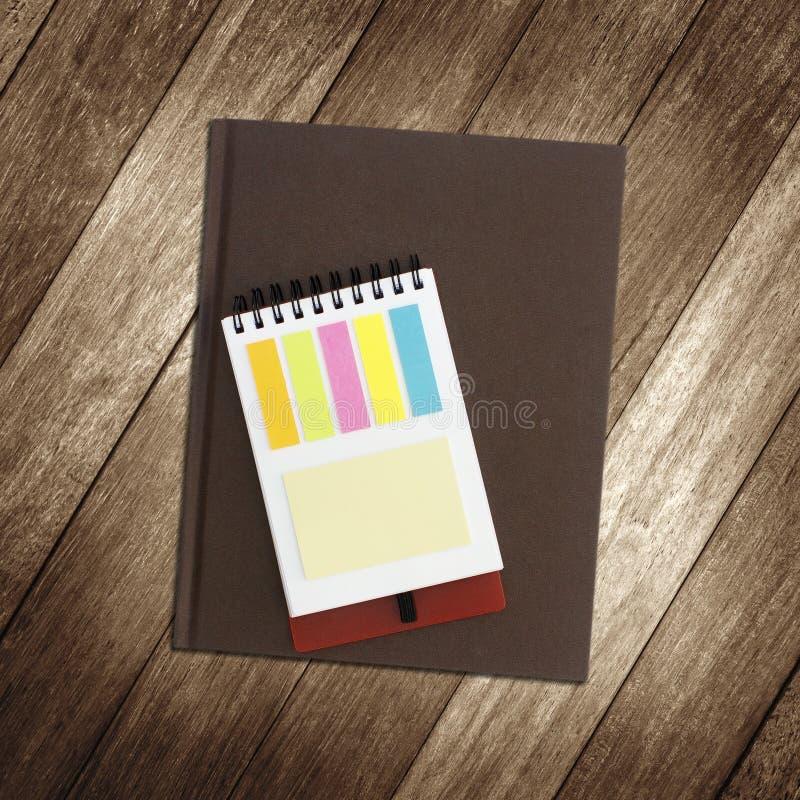 Тетрадь и notepaper на деревянной предпосылке стоковые фото