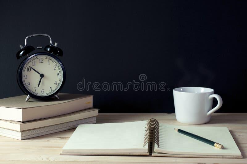 Тетрадь, карандаш, книги, чашка кофе и часы рабочего места стоковое изображение