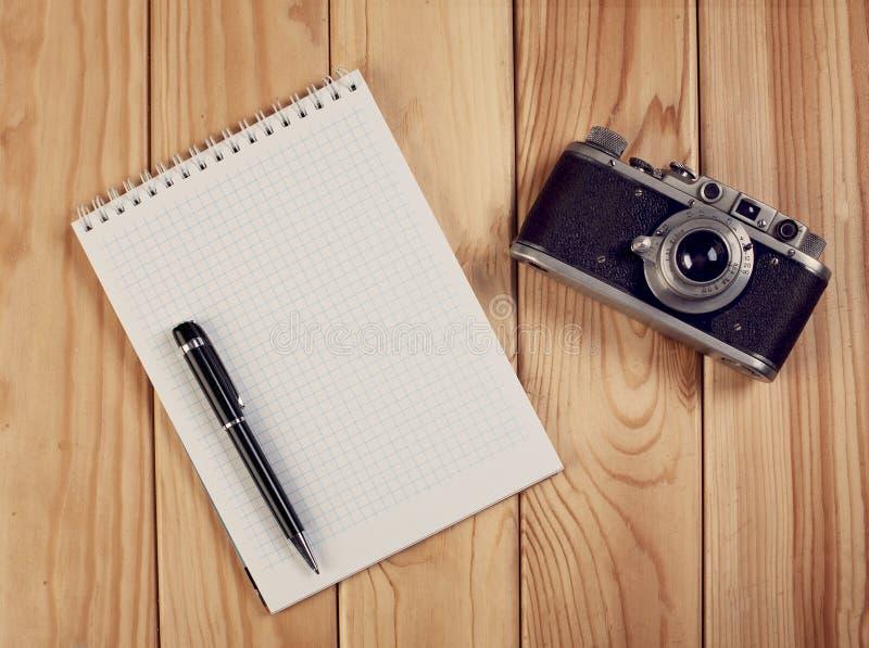 Тетрадь с камерой ручки и года сбора винограда на деревянном столе Взгляд сверху стоковые изображения rf