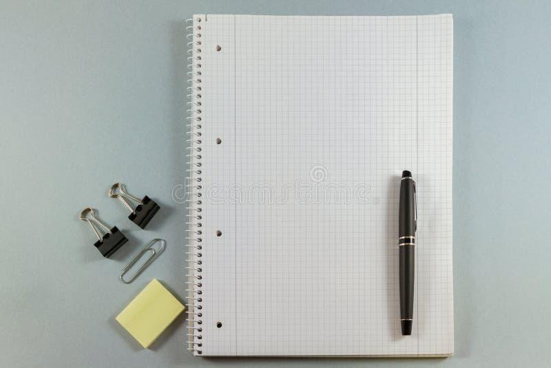 Тетрадь с чистым листом бумаги, красит липкие примечания, ручку и зажимы дальше стоковая фотография