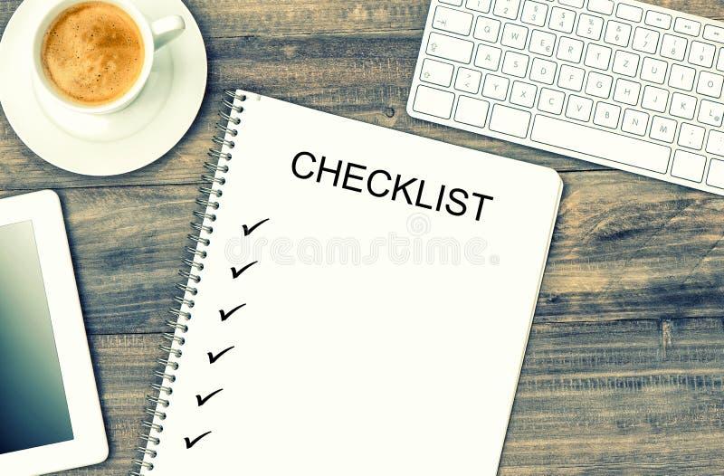 Тетрадь, цифровая таблетка, клавиатура и кофе Насмешка вверх по контрольному списоку стоковое изображение