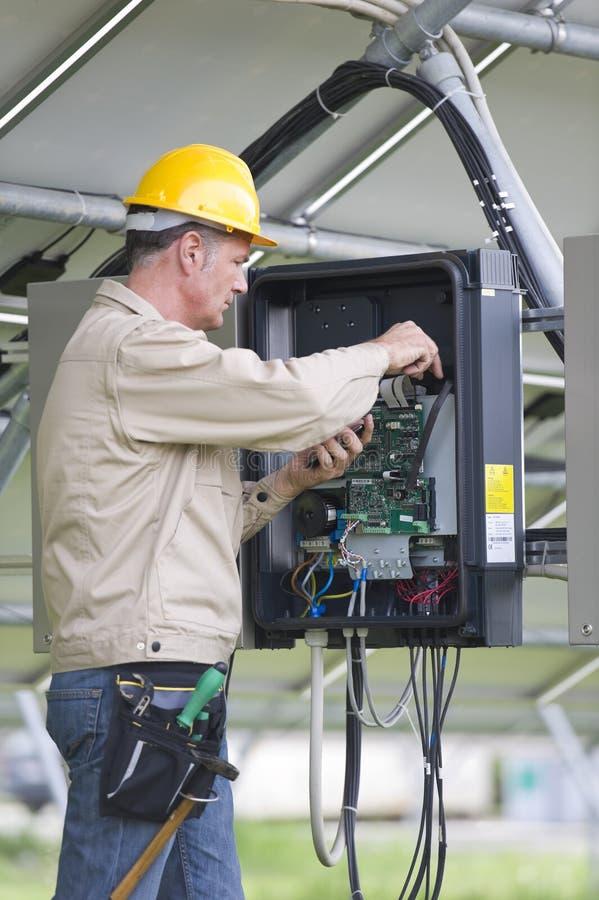 Техники работая под панелями солнечных батарей стоковые фото
