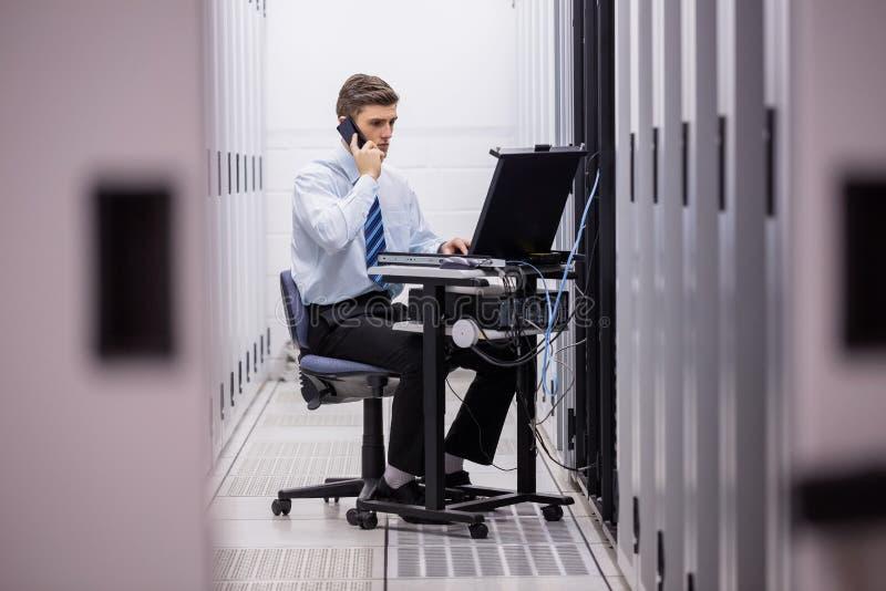 Техник говоря на телефоне пока диагностирующ серверов стоковые изображения
