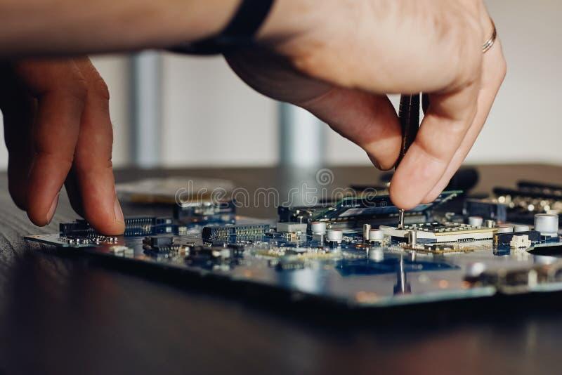 Техник затыкает внутри микропроцессор C.P.U. к материнской плате компьютера стоковые фото