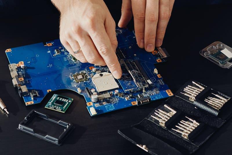 Техник затыкает внутри микропроцессор C.P.U. к материнской плате компьютера стоковая фотография rf