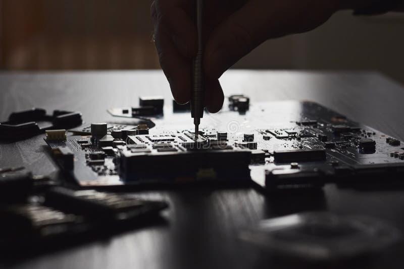 Техник затыкает внутри микропроцессор C.P.U. к материнской плате компьютера стоковая фотография