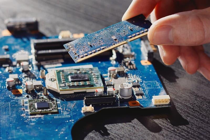 Техник затыкает внутри память к материнской плате компьютера стоковое фото