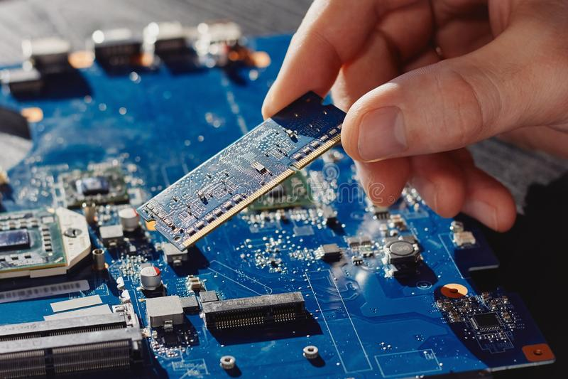 Техник затыкает внутри память к материнской плате компьютера стоковая фотография