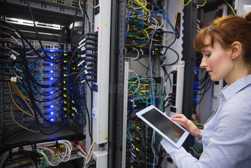 Техник используя ПК таблетки пока анализирующ сервера стоковая фотография