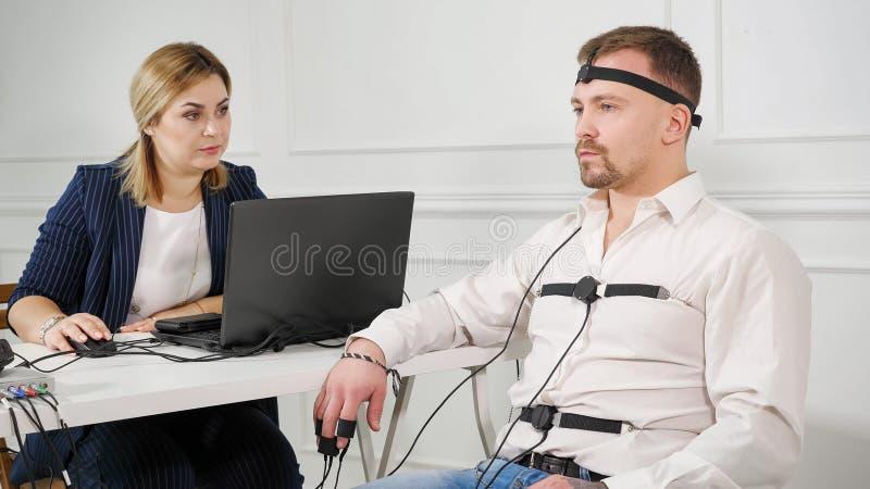 Техник полиграфа читает вопросы от ноутбука Человек соединенный к цепи детектора лжи стоковое фото