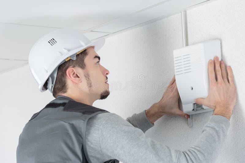 Техник проверяет охранную сигнализацию в профессиональном здании стоковое изображение