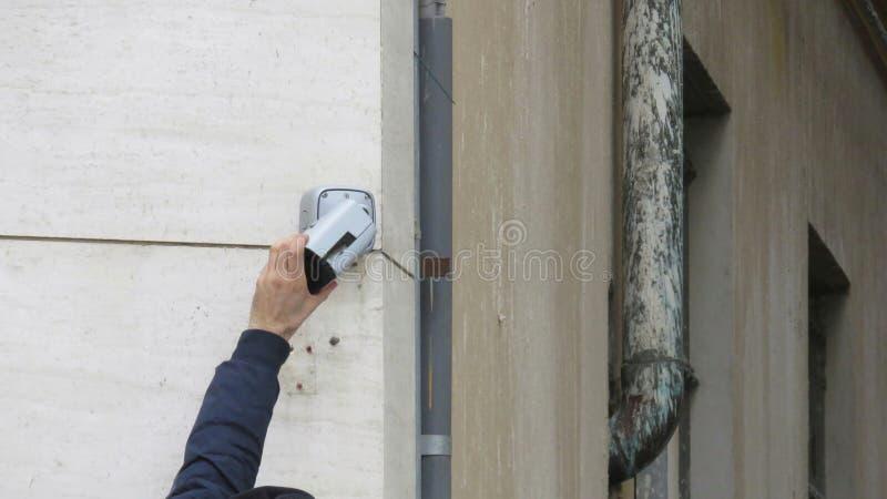 Техник ремонтирует систему охраны стоковое изображение