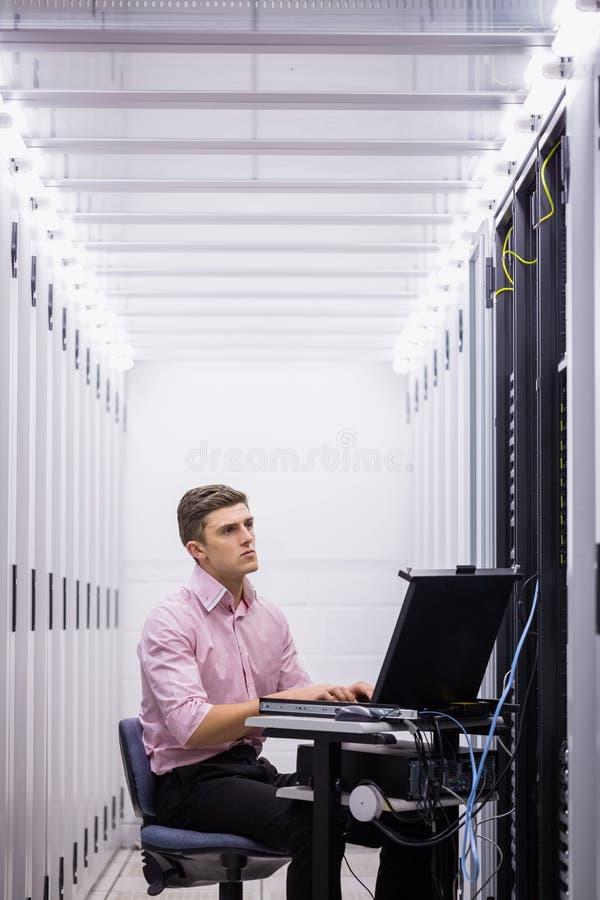 Техник сидя на вращающееся кресло используя компьтер-книжку для того чтобы диагностировать серверов стоковые фотографии rf