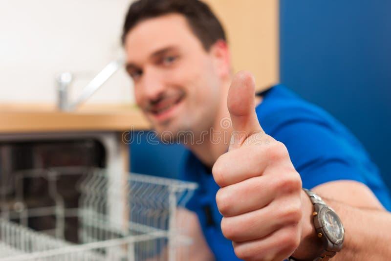 техник судомойки ремонтируя стоковое фото rf