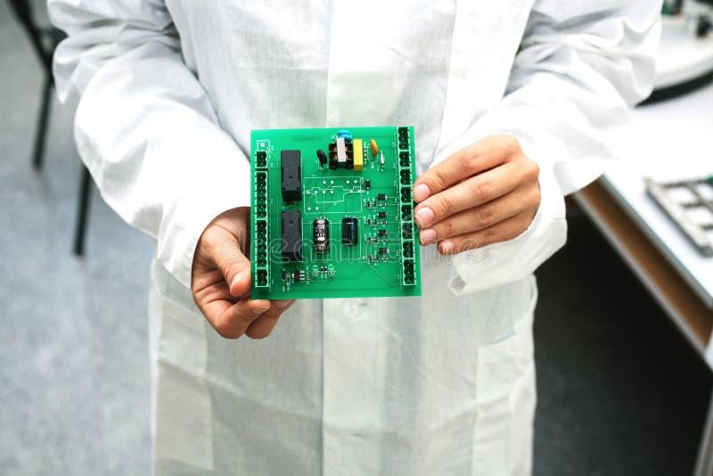 Техник с монтажной платой компьютера с обломоками Запасные части и компоненты для компьютерного оборудования Продукция  стоковое фото rf