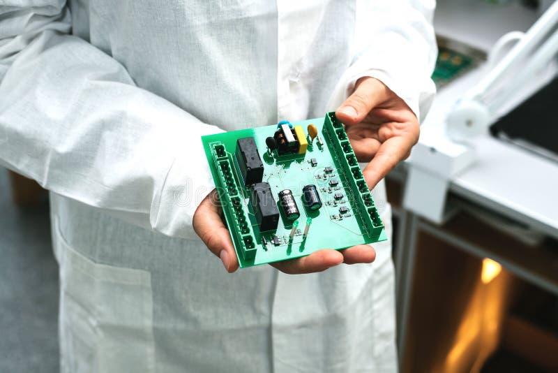 Техник с монтажной платой компьютера с обломоками Запасные части и компоненты для компьютерного оборудования Продукция  стоковое изображение rf