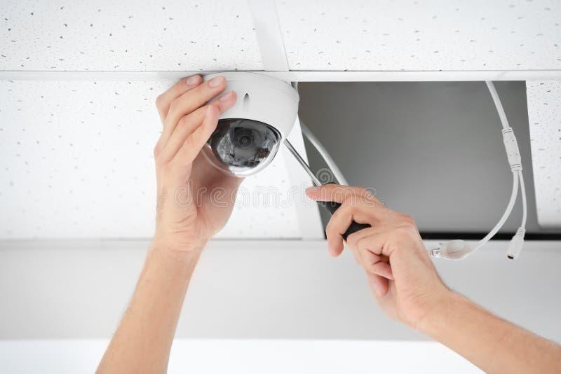 Техник устанавливая камеру CCTV на потолок внутри помещения стоковые фото