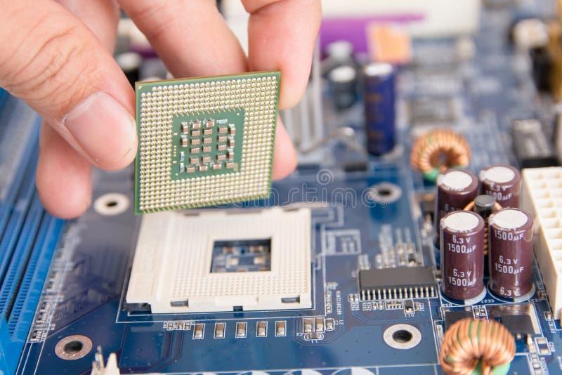 Техник устанавливая микропроцессор обломока C.P.U. к гнезду на mothe стоковое изображение rf