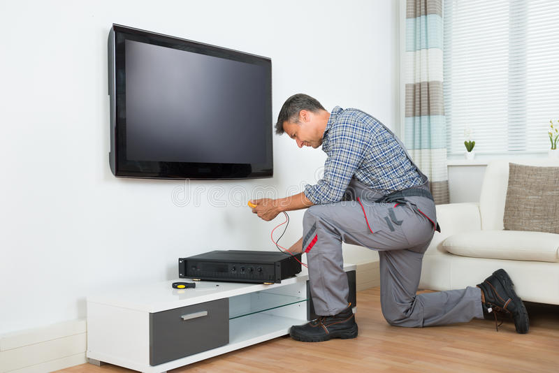 Техник устанавливая коробку телевизора верхнюю дома стоковая фотография rf