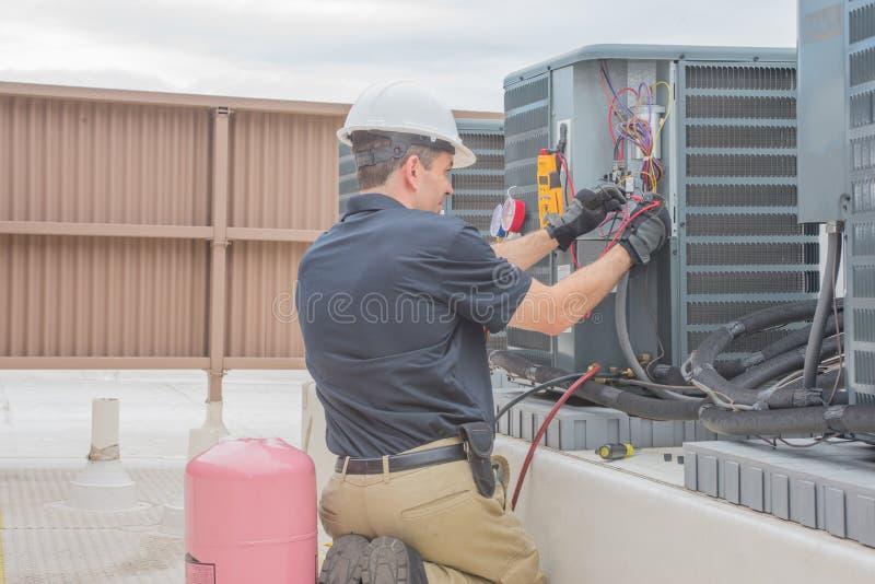 Техник HVAC проверяя конденсатор стоковая фотография