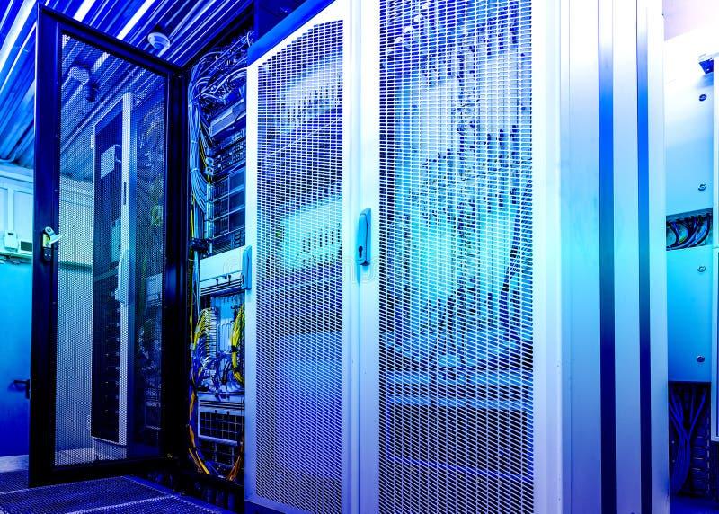 Техническая стена строк клетчатых данных терминальных с раскрытой дверью сетки тонизировать современного центра данных голубой стоковое изображение rf