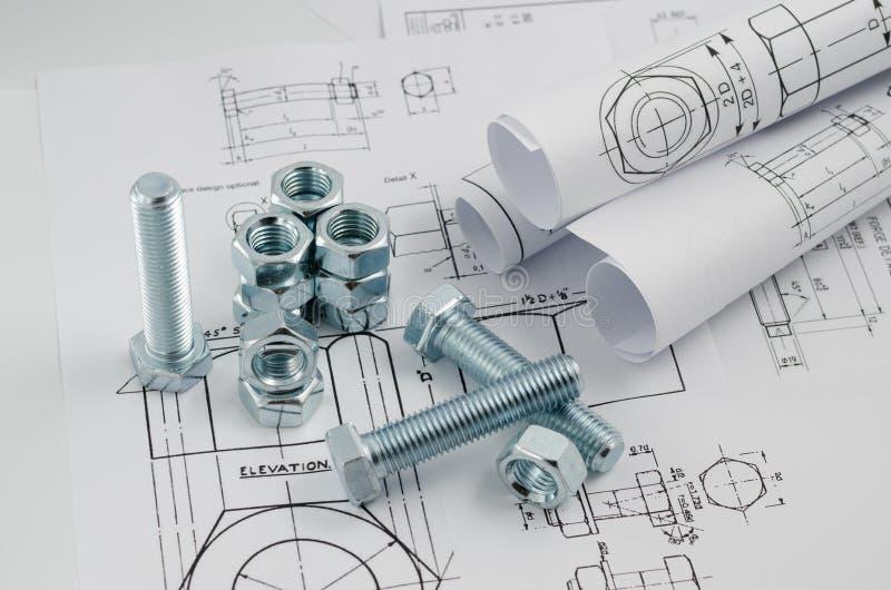 Технология машиностроения Гайки - и - болты на бумажных чертежах стоковое фото rf