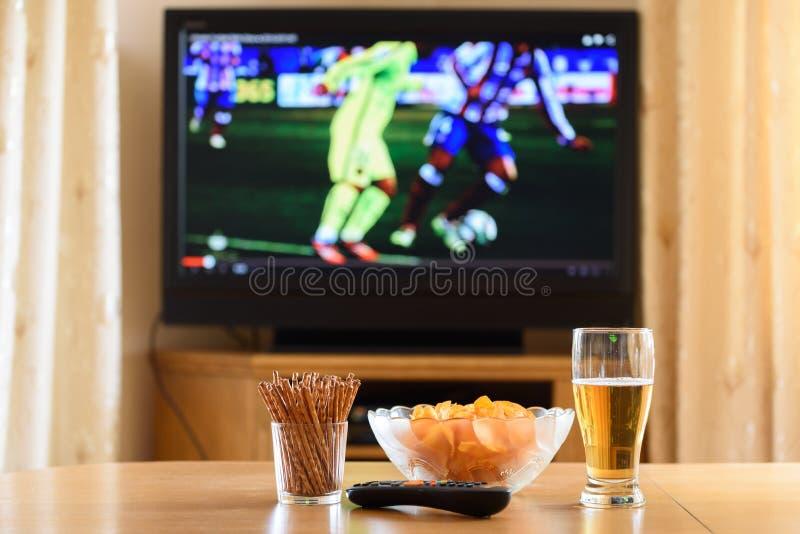 Телевидение, ТВ смотря (футбол, футбольный матч) с lyi закусок стоковое изображение