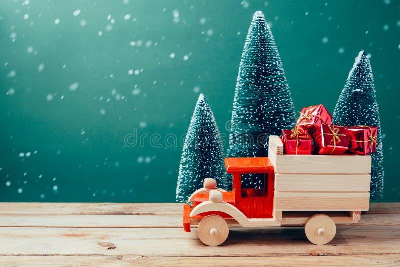 Тележка игрушки рождества с подарочными коробками и сосной на деревянном столе над зеленой предпосылкой стоковое фото rf