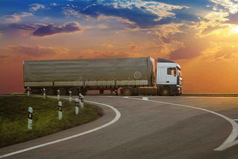 Тележка идет на шоссе на заходе солнца стоковое изображение