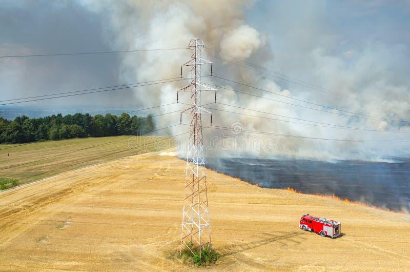 Тележка пожарного работая на поле на огне стоковая фотография