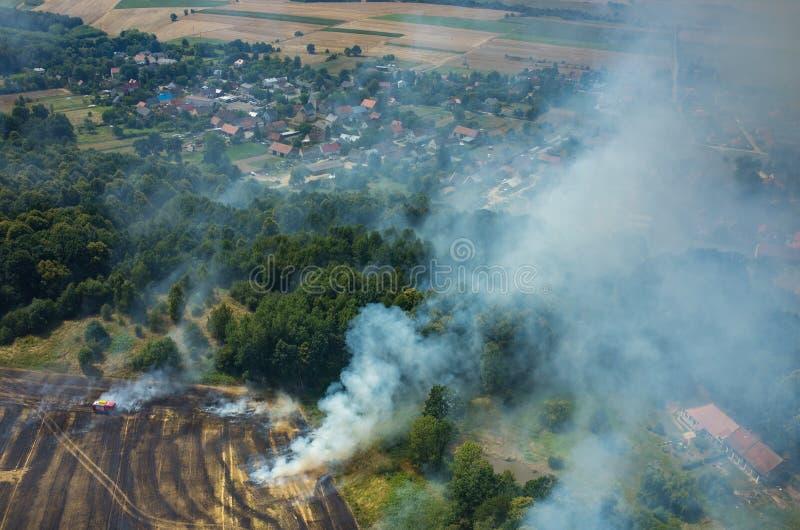 Тележка пожарного работая на поле на огне стоковое фото