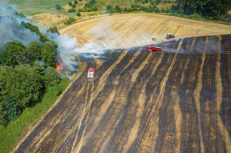 Тележка пожарного работая на поле на огне стоковое фото rf