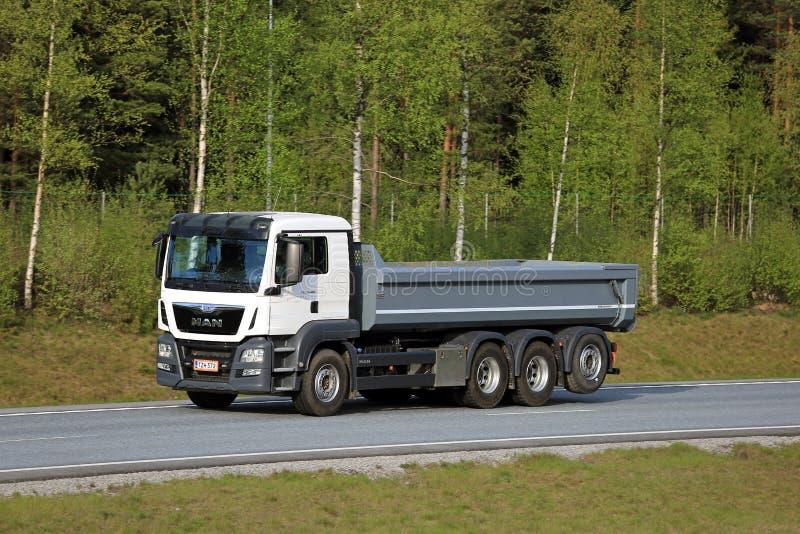 Тележка Tipper ЧЕЛОВЕКА на шоссе с предпосылкой леса стоковая фотография rf