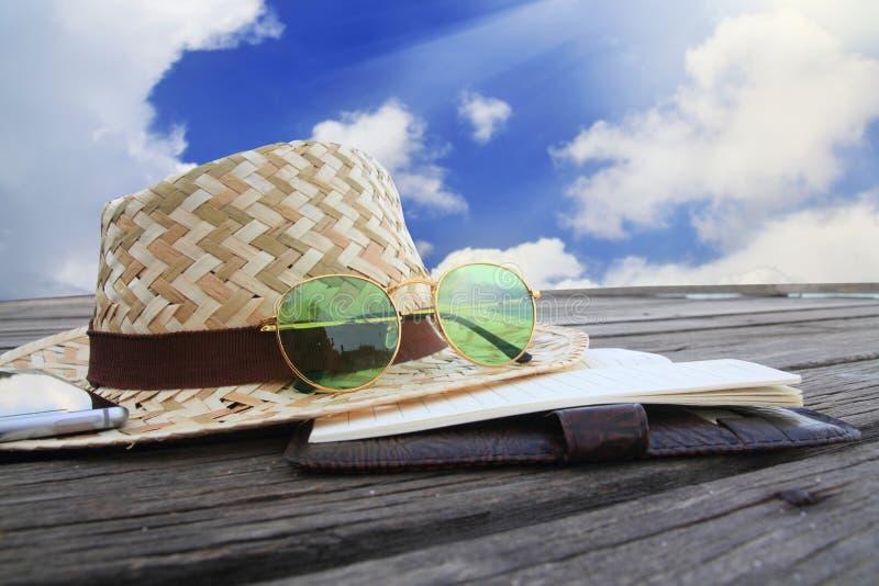 Телефонируйте, зеленые солнечные очки и соломенная шляпа на деревянном мосте стоковое изображение
