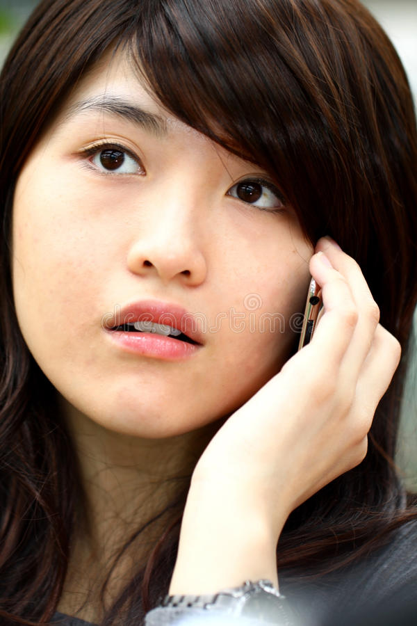 Телефон азиатской женщины говоря стоковые изображения