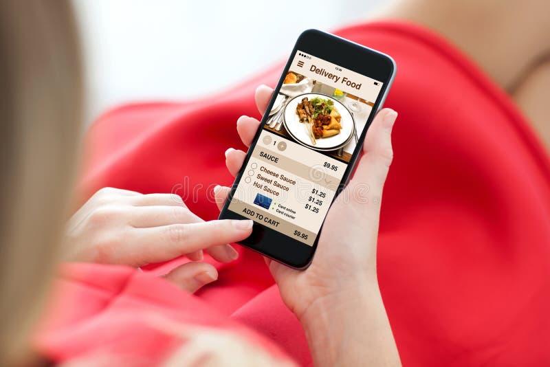 Телефон касания удерживания женщины с экраном еды поставки app стоковые фото