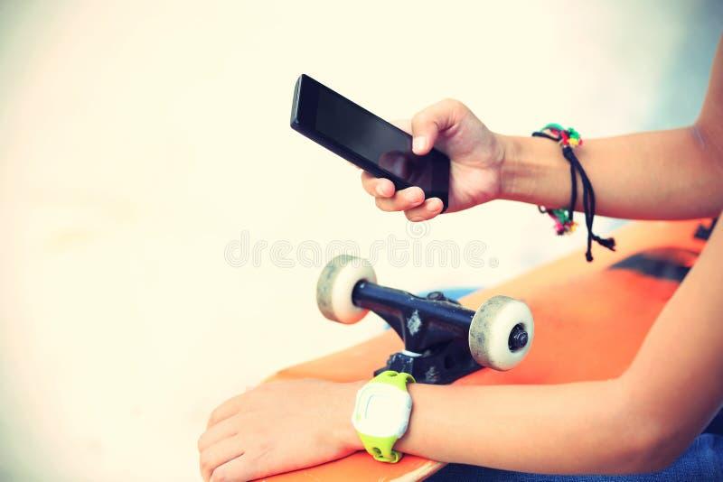 Телефон пользы скейтбордиста молодой женщины умный в городе стоковое изображение