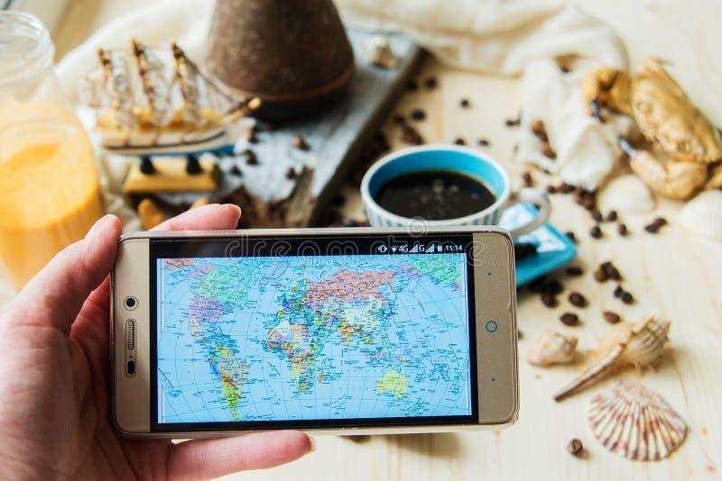 Телефон прессы руки умный с кофейной чашкой и наушником, концепцией все может сделать на вашей руке умным телефоном, взгляд сверх стоковая фотография rf