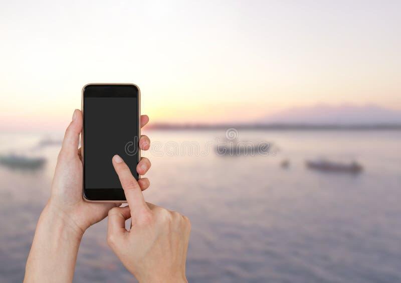 Телефон руки касающий рядом с ландшафтом моря стоковые фото