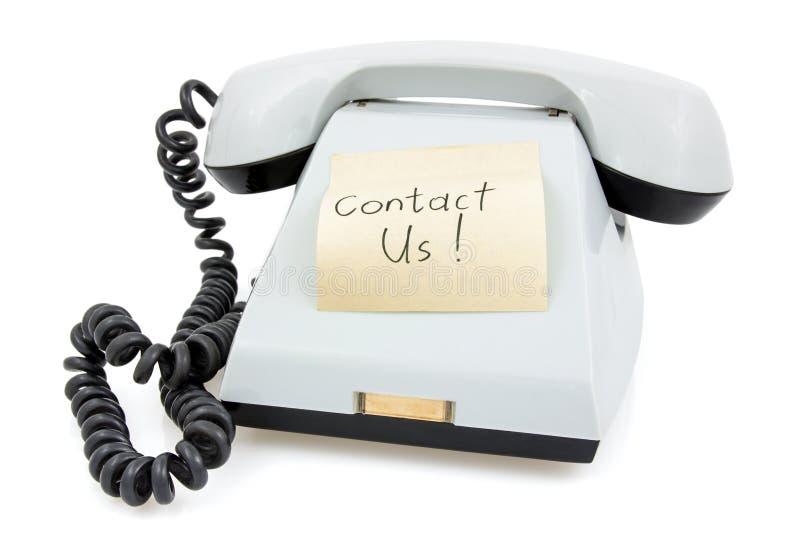 Телефон с липким примечанием свяжется мы стоковое изображение