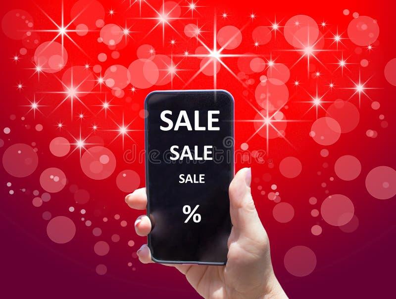 Телефон с ПРОДАЖЕЙ текста в женской руке на красной предпосылке стоковая фотография