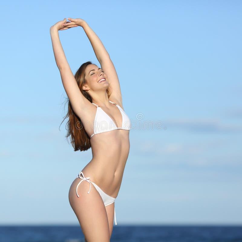 Тело женщины фитнеса при белое бикини представляя на пляже стоковые изображения
