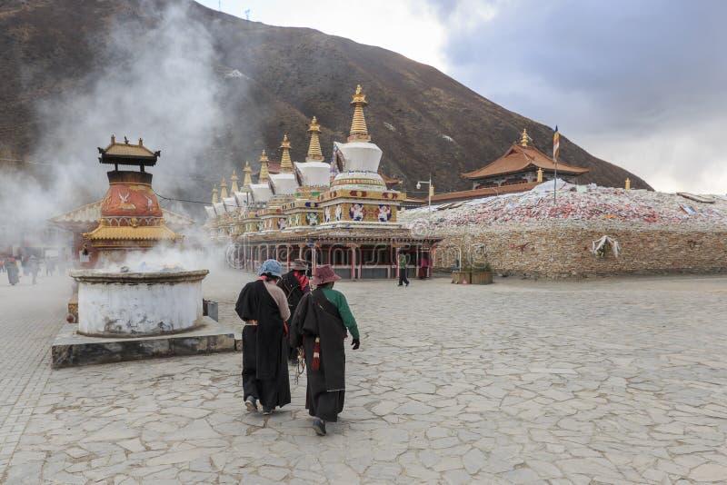 Тибетские люди идя вокруг виска Mani Shicheng Mani известный ориентир ориентир в тибетском городе Yushu Jyekundo, Цинхая, Chin стоковое изображение rf